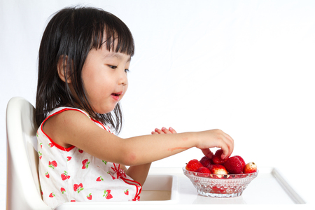 kids eating healthy: Asian Chinese children eating strawberries in plain white background.