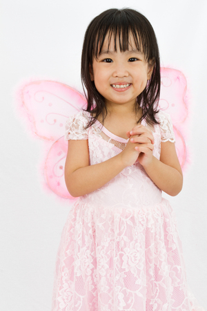 butterfly  angel: Chinese little girl wearing butterfly custome with praying gesture in plain white background