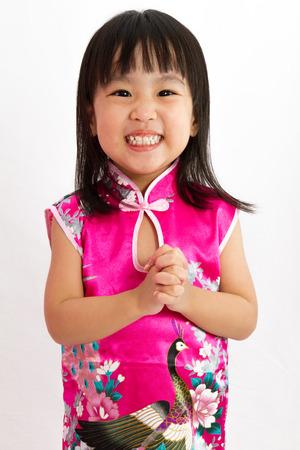 ni�as peque�as: Ni�a china llevaba cheongsam con gesto de saludo en fondo blanco llano.