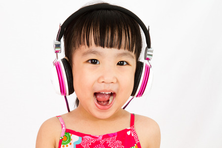 girl open mouth: Chinese little girl on headphones with mouth open
