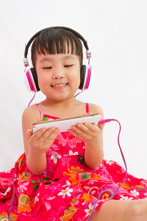 mobile phones: Chinese little girl on headphones holding mobile phone in plain isolated white background. Stock Photo