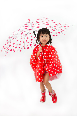 Chinese Little Girl Holding umbrella with raincoat in plain white isolated background. Stock Photo