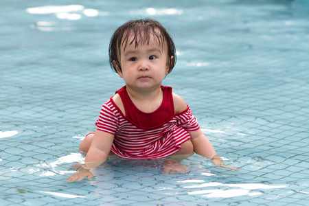 baby swimming: Chinese Little Girl Playing in Water in Swimming Pool
