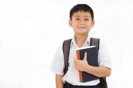 アジア学校坊やを抱きかかえて白い背景の上のバックパックと書籍