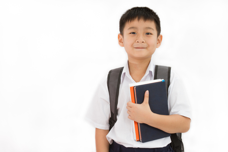 Asiatische Kleine Schule Jungen-Holding-Bücher mit Rucksack auf weißem Hintergrund