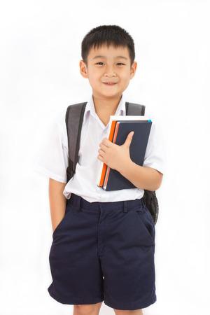 Asiatiques petite école garçon tenant livres avec sac à dos sur fond blanc Banque d'images