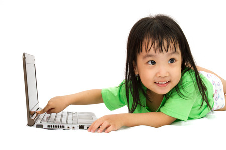 girl lying down: Chinese little girl lying down with laptop in plain white isolated background. Stock Photo