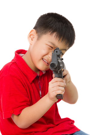 asian warrior: Asian Little Boy Playing Plastic Toy AK47 on White Background Stock Photo