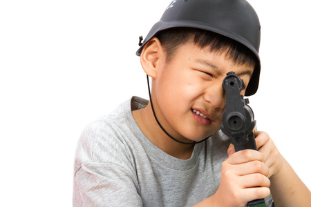 police helmet: Asian Little Boy Playing Plastic Toy AK47 with Police Helmet on White Background
