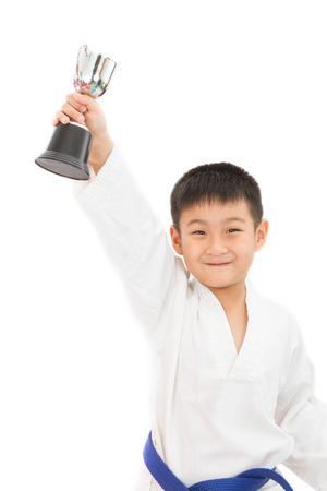premios: Poco asiático del muchacho del karate que sostiene la taza en el kimono blanco sobre fondo blanco