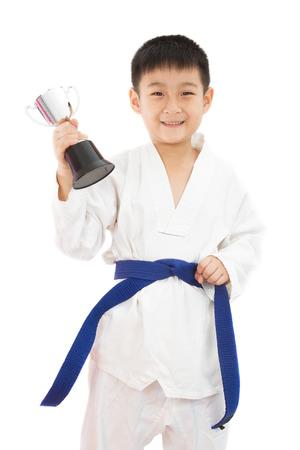 deportistas: Poco asiático del muchacho del karate que sostiene la taza en el kimono blanco sobre fondo blanco