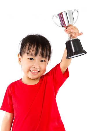 trofeo: Niña Asiática Chino Smiles con un trofeo en sus manos aisladas en el fondo blanco. Foto de archivo