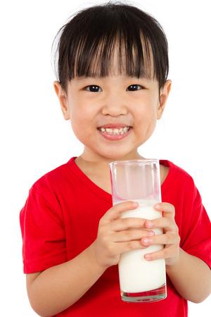 tomando leche: Poco asiático de la muchacha china que sostiene una taza de leche aislado en el fondo blanco