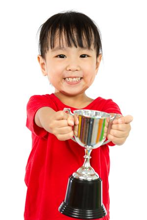 deportistas: Niña Asiática Chino Smiles con un trofeo en sus manos aisladas en el fondo blanco. Foto de archivo