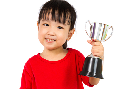 reconocimientos: Niña Asiática Chino Smiles con un trofeo en sus manos aisladas en el fondo blanco. Foto de archivo