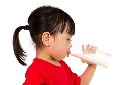 Asian Little Chinese Girl Drinking a cup of Milk isolated on White Background 스톡 콘텐츠