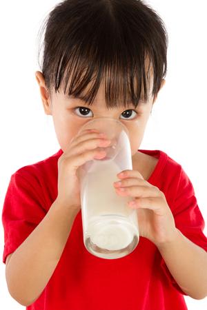 cute teen girl: Азиатский Маленькая китайская девушка пить стакан молока, изолированных на белом фоне Фото со стока