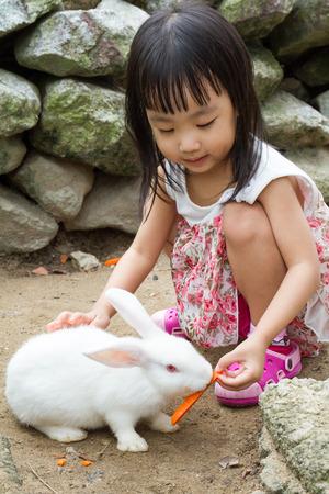 Niña asiática china Alimentar a un conejo con la zanahoria en la granja