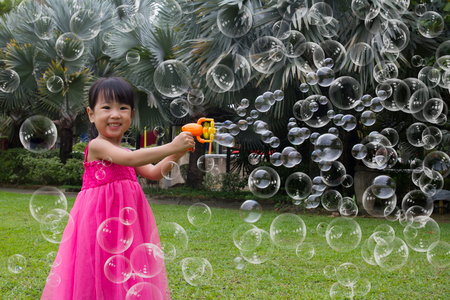 happy little girl: Asian Little Chinese Girls Shooting Bubbles from Bubble Blower in the Park Stock Photo