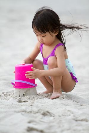 traje de bano: Poco asi�tico ni�a china que juega la arena con los juguetes de playa en la playa tropical Foto de archivo