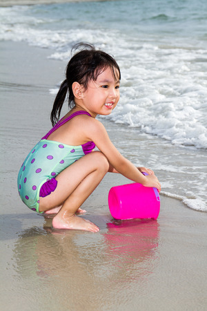 little people: Asian Little Chinese Girl Playing Sand with Beach Toys on Tropical Beach