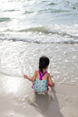 little girl swimsuit: Asian Little Chinese Girl Playing Sand with Beach Toys on Tropical Beach