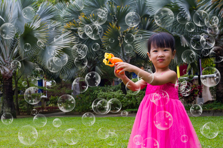 niñas chinas: Asian Little Chinese Girls Shooting Bubbles from Bubble Blower in the Park Foto de archivo