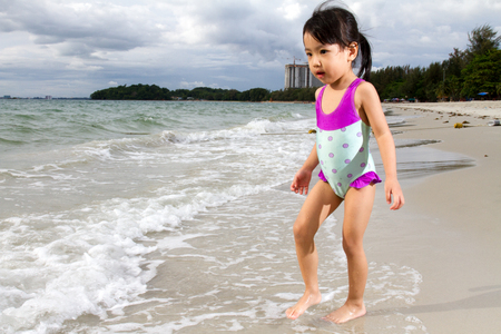 little girl beach: Asian Little Chinese Girl Playing in Swimsuit on Tropical Beach