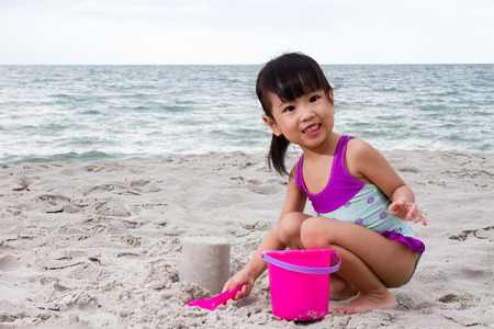 beach toys: Asian Little Chinese Girl Playing Sand with Beach Toys on Tropical Beach