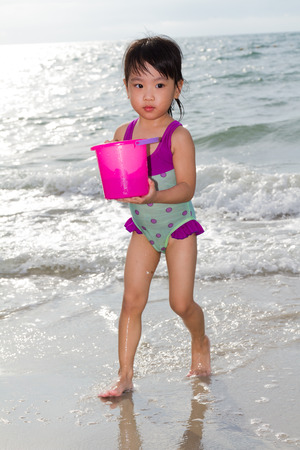 traje de bano: Ni�a Asi�tica China Jugando con juguetes de playa en la playa tropical