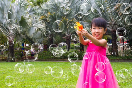 Asian Little Chinese Girls Shooting Bubbles from Bubble Blower in the Park Stock Photo