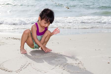 arena: Poco asiático niña china que juega la arena en la playa tropical