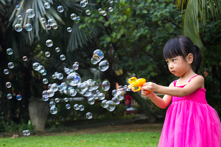 ni�as chinas: Asian Little Chinese Girls Shooting Bubbles from Bubble Blower in the Park Foto de archivo