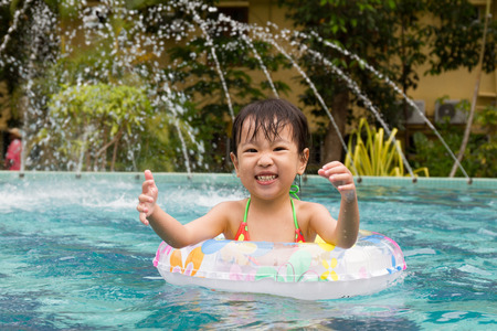 little girl swimsuit: Asian Little Chinese Girl Playing in Swimming Pool with Swimming Circle