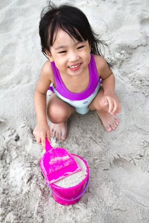 ni�as peque�as: Poco asi�tico ni�a china que juega la arena con los juguetes de playa en la playa tropical Foto de archivo