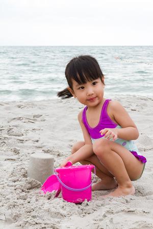 traje de baño: Poco asiático niña china que juega la arena con los juguetes de playa en la playa tropical Foto de archivo