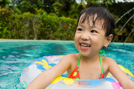 cute girl: Asian Little Chinese Girl Playing in Swimming Pool with Swimming Circle