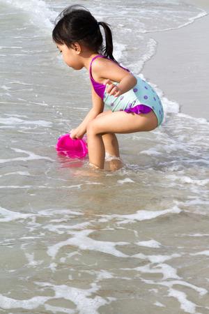 niñas pequeñas: Poco asiático niña china que juega la arena con los juguetes de playa en la playa tropical Foto de archivo