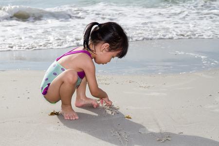 niñas jugando: Poco asiático niña china que juega la arena en la playa tropical