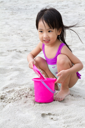 little girl beach: Asian Little Chinese Girl Playing Sand with Beach Toys on Tropical Beach