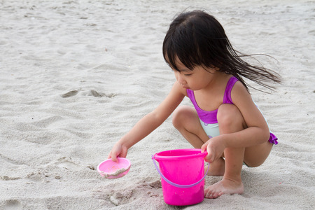 swimming costumes: Asian Little Chinese Girl Playing Sand with Beach Toys on Tropical Beach
