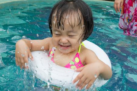 ni�as peque�as: Ni�a asi�tica china que juega en piscina con los Nataci�n C�rculo Foto de archivo