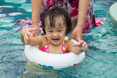 teenager girl: Asian Little Chinese Girl Playing in Swimming Pool with Swimming Circle