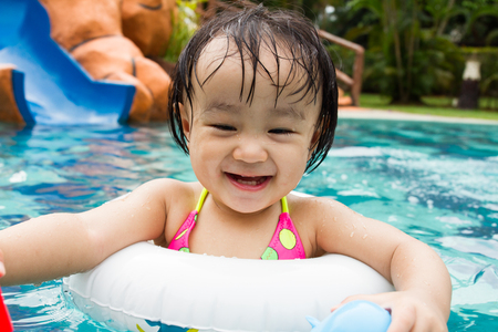 happy little girl: Asian Little Chinese Girl Playing in Swimming Pool with Swimming Circle