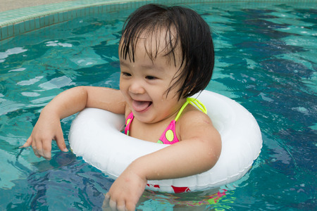 little people: Asian Little Chinese Girl Playing in Swimming Pool with Swimming Circle