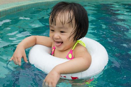 traje de bano: Ni�a asi�tica china que juega en piscina con los Nataci�n C�rculo Foto de archivo