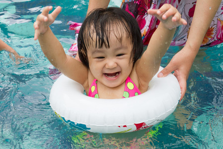 jolie jeune fille: Asian Little Chinese Girl Playing in Swimming Pool with Swimming Circle