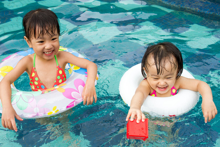 asia children: Asian Little Chinese Girls Playing in Swimming Pool with Swimming Circle
