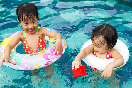 niñas chinas: Asian Little Chinese Girls Playing in Swimming Pool with Swimming Circle
