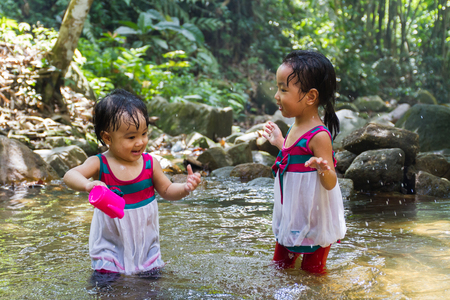 bourne: Asian Little Chinese Girls Playing in Creek in the Forest Stock Photo